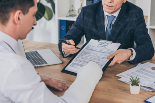 An attorney helping an injured man fill out a Workers' Compensation form